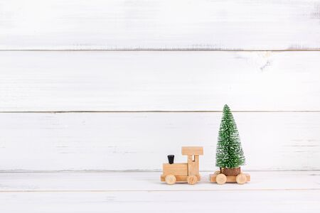 Pine tree with wooden toy train on white wood background with copy space