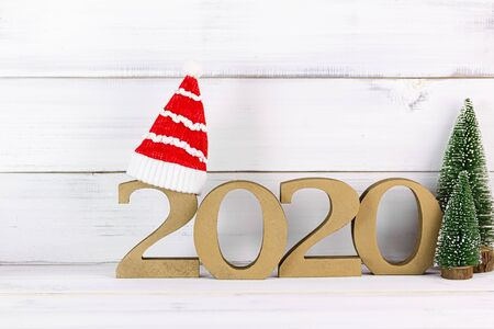 Upcoming 2020 New Year with Christmas tree and christmas hat over white wood background.