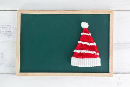 Christmas hat with empty black board on white wood background.