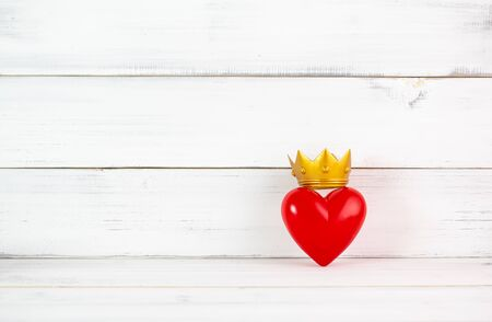 Red Heart Shaped with Golden Crown over white wood background. Symbol for queens or kings of lover , health concept with copy space. Stock Photo