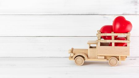 Red Heart Rubber on Wooden Toy Truck over white background. Love Concept with Copy Space.