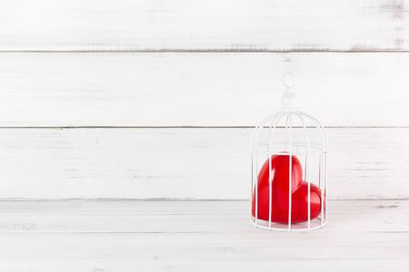 Red Heart inside Bird Cage on white wood background. Freedom Love with Copy Space.