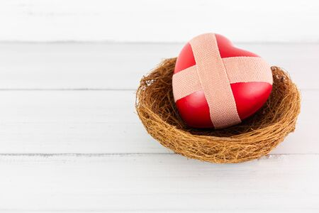 Red Heart with Cross Plaster inside bird nest on white wood background. Protect Pain of Love with Copy Space. Stock fotó
