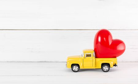 Red Heart on Toy Yellow Pickup Car on white wood background. Travel Love Concept with Copy Space.