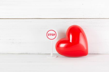Stop Sign with Read Heart on white wood background. Broken Love Concept with Copy Space.