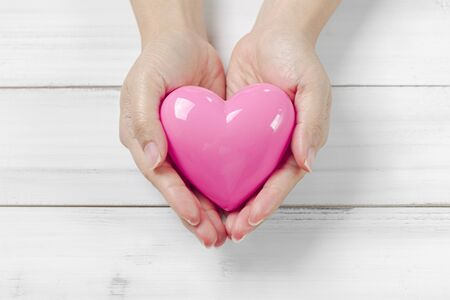 Man Hands Hold Pink Heart on white wood background. Giving love concept.