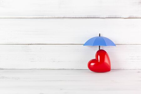 Red Heart under Umbrella on white wood background. Proect love or Heart Concept with Copy Space.