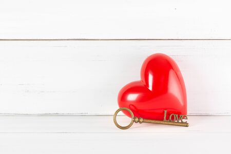 Red Heart with Antique Key on white wood background. Success Love Concept with Copy Space. Stock fotó