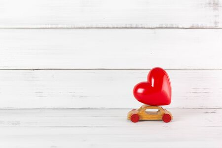 Red Heart on Wooden Toy Car on white wood background. Love Travel Concept with Copy Space.