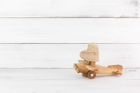 Wooden Heart on Wooden Toy Plane over white wood background.  Fly to love concept with copy space.