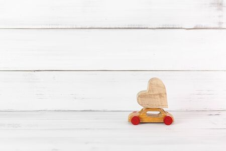 Wooden Heart on Wooden Toy Car on white wood background. Love Travel Concept with Copy Space. Stock fotó