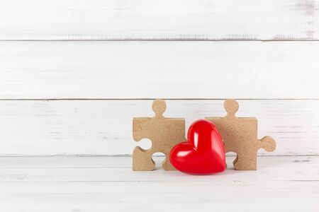 Red Heart with Wooden Puzzle Jigsaw on white wood background. Relations of Love concept with Copy Space.