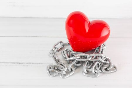 Red Heart with Chain on white wood background with Copy Space. Stock fotó