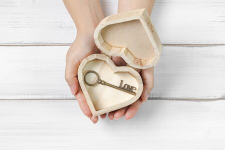 Woman Hands Hold Antique Key Love inside Heart Box on white wood background. Success Love Concept with copy space.
