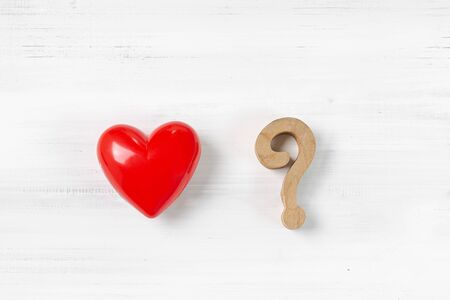 Question Mark and Red Heart on white wood background. Solving Problem of Love Concept.