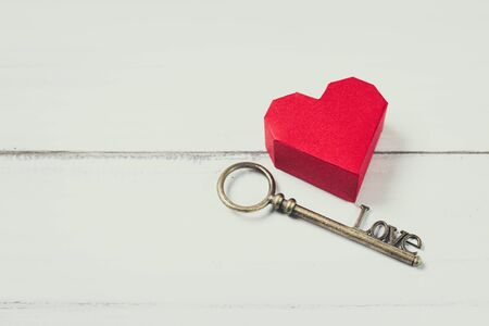 Red Paper Heart with Antique Key on white wood background. Success Love Concept with Copy Space. Stock fotó