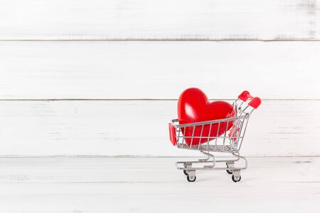 Red Heart in Trolley Shopping Cart  over white wood background. Love Concept with Copy Space. Stock fotó