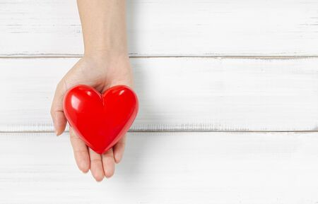 Woman Hand Hold Red Heart on white wood background. Protect Love or Health Concept with Copy Space. Stock fotó