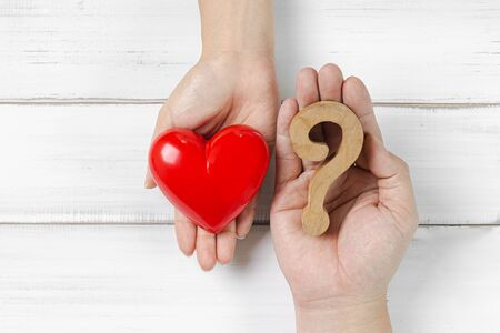 Woman Hand and Man Hand Hold Question Mark and Red Heart on white wood background. Couple Solving Problem of Love Concept. Stock fotó