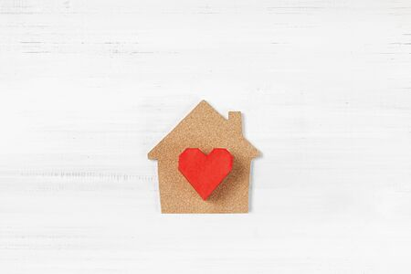 Red Paper Heart with House shaped on white wood background. Happy home concept with copy space.