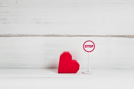 Stop Symbol with Read Paper Heart on white wood background. Broken Love Concept with Copy Space.