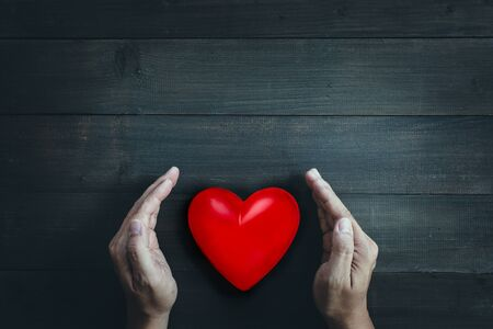 Hands protect red heart on wood table background. Save health or love  concept.