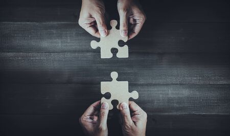 Hands holding wooden jigsaw puzzle pieces and solving put pieces of the puzzle together. Business solving , Teamwork and partnership concept. Stock fotó