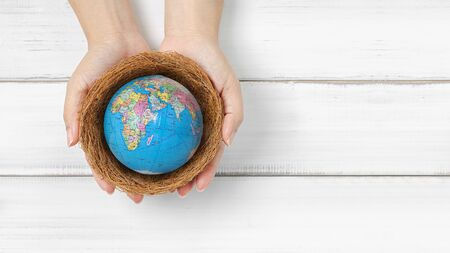 Woman hands hold the globe on bird nest over white wood background with copy space. protect and save our world from  disease pandemic , air pollution and humans damaging the environment. Stock fotó
