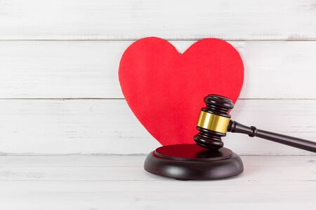 Judge Gavel Hammer with Red Heart on white wood background. Family or Love of Law Concept with Copy Space.