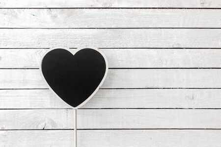 Heart Blackboard Shaped over white wood background
