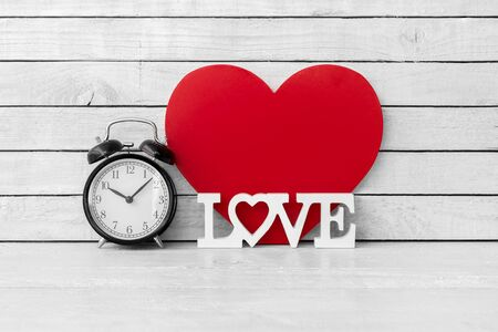 Alarm Clock with Love Alphabet and Red Heart Shaped on white wood over white wood background