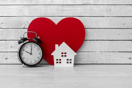Home Shaped with Red Heart Shaped and Alarm clock on white wood over white wood background