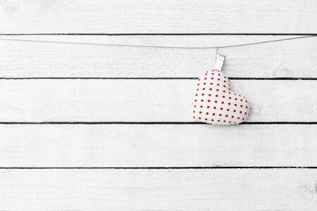 Heart Fabric hang over white wood background Standard-Bild