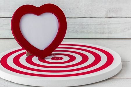 Red Heart Frame on Red dartboard over white wood background