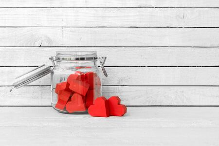 Red Heart Shaped made from paper in bottle glass over white wood background