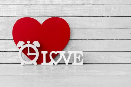 Clock Shaped with Love Alphabet and Red Heart Shaped on white wood over white wood background Zdjęcie Seryjne