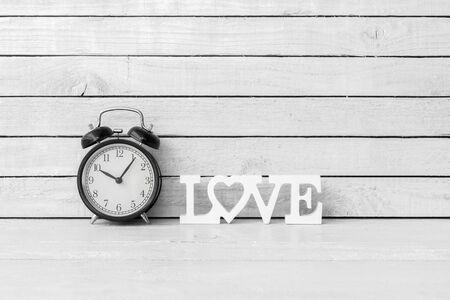 Alarm Clock with Love Alphabet on white wood over white wood background