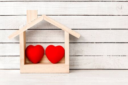 Wood Home Shaped with red heart shaped on white wood over white wood background.