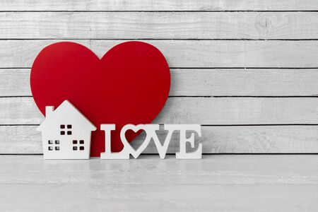 Home Shaped with Love Alphabet and Red Heart Shaped on white wood over white wood background