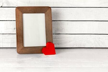 Photo Frame with Red Heart Paper on table over white wood background