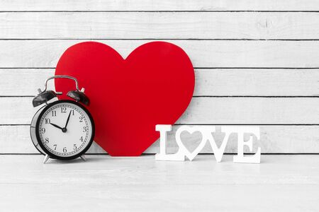 Red Heart Shaped with Alarm Clock on white wood over white wood background Zdjęcie Seryjne