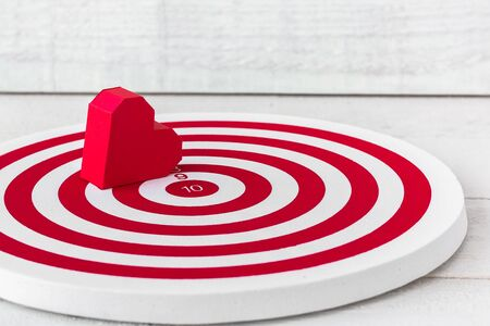 Red Heart Paper Shaped on Red dartboard over white wood background 免版税图像