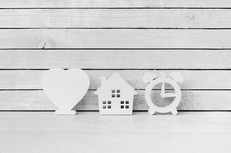 White Heart Shaped with Clock Shaped and Home Shaped on white wood over white wood background
