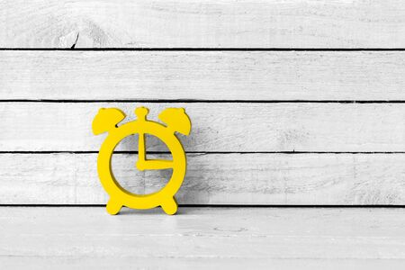 Yellow Alarm Clock Shaped on white wood Background Standard-Bild