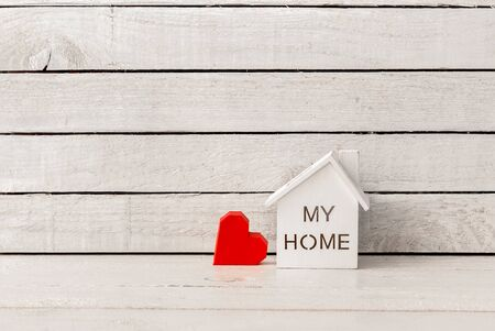 My Home Shaped with red paper heart on white wood over white wood background.