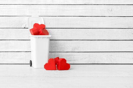 Red Heart Shaped made from paper in bins over white wood background