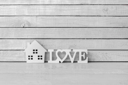 Home Shaped with Love Alphabet on white wood over white wood background Standard-Bild
