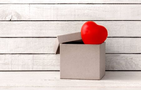 Red Heart Shaped with brown gift box over white wood background Standard-Bild