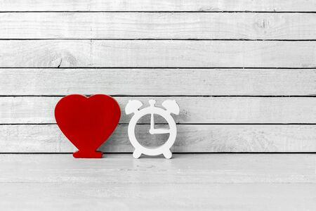 Red Heart Shaped with Clock Shaped on white wood over white wood background