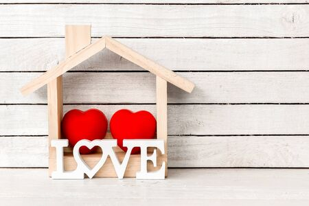 Wood Home Shaped with red heart and love alphabet shaped on white wood over white wood background. 免版税图像